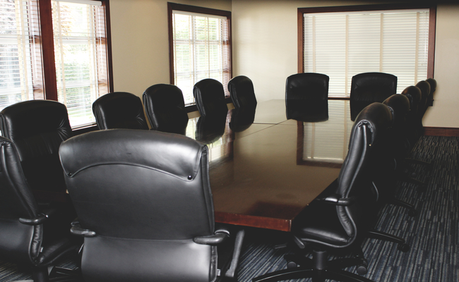 A picture of a conference room with a clean table and chairs